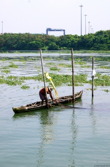 Fisherman docking boat to lower his nets