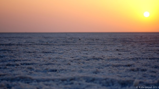 The sun sets on the horizon of the Salt Desert